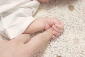 大きな指を握りしめる赤ん坊の手の画像